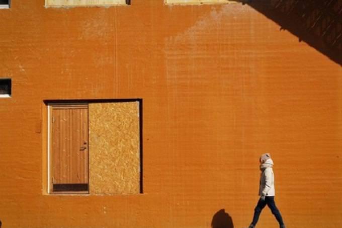 Homem andando perto da parede de laranja