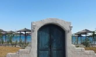 door built into a wall on the beach