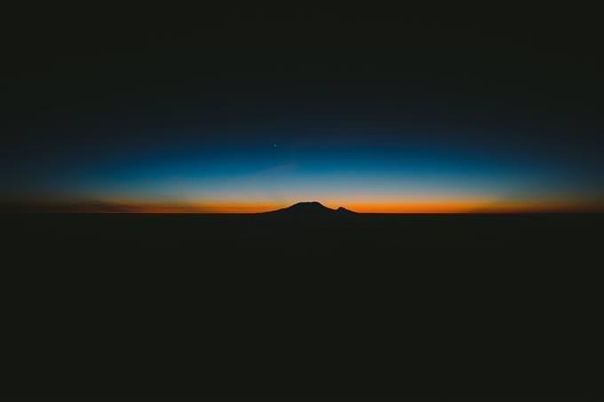 Luz anaranjada contra el cielo y una sombra de montañas