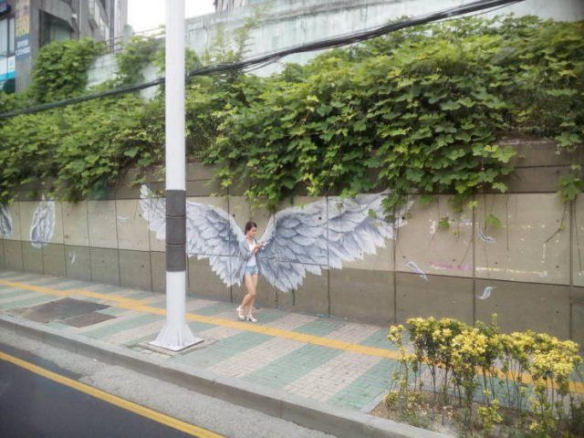 Photo taken at just the right time, girl on cell phone in from of grafitti wings