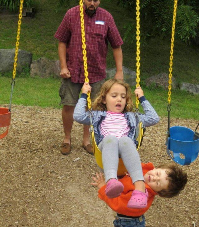 Photo taken at just the right time, little girl on swings kicks young boy