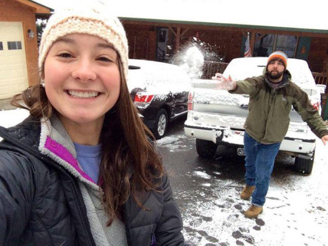 Photo taken at just the right time, girl taking a selfie as guy throws a snowball at her