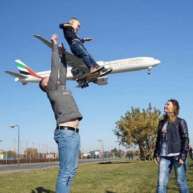 Photo taken at just the right time, parents playing with child while airplane passes in the background