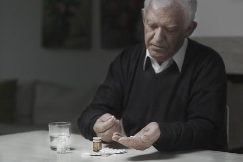 senior man taking pain medication
