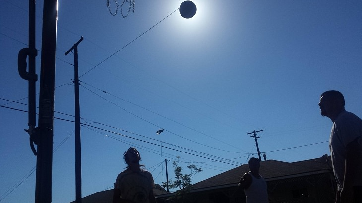 Perfectly-timed photographs, people playing basketball, with the basketball covering the sun forming an eclipse