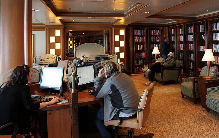Tips for making the most of your next cruise trip, people sitting at computers in a cruise ship library