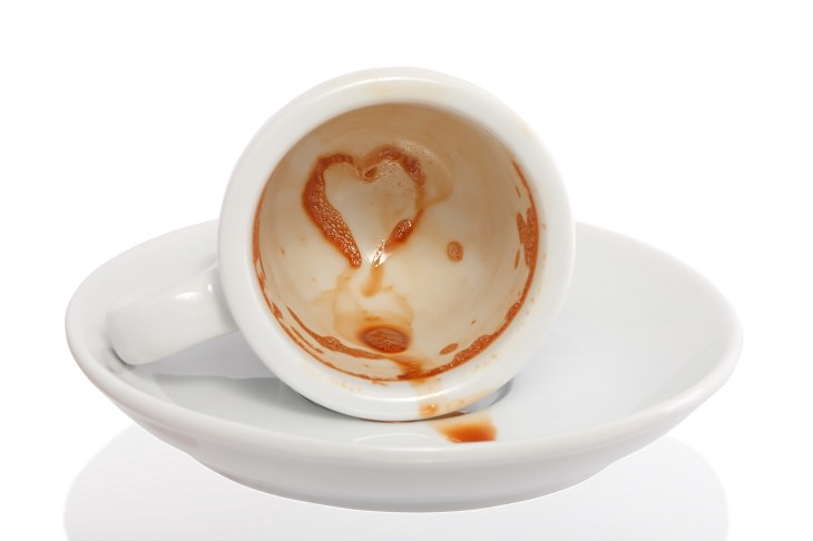 Different coffee stain removal methods, white coffee mug on its side on a white saucer with brown stains inside the mug, one shaped as a heart