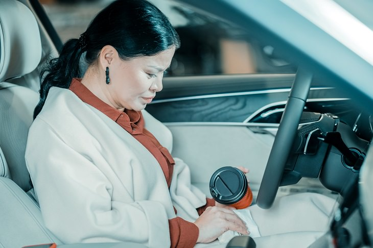Different Coffee Stain Removal Methods, Brunette woman in a white coat sitting in her car holding a coffee flask