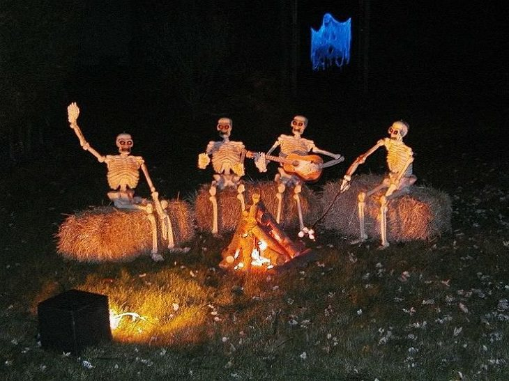 Most Incredible Halloween Decorations, skeletons sitting on hay around a bonfire, one playing guitar