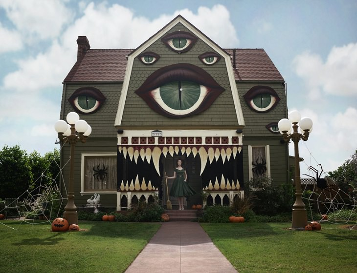Most Incredible Halloween Decorations, Monster house with multiple eyes, sharp teeth and a witch with a broomstick standing at the entrance