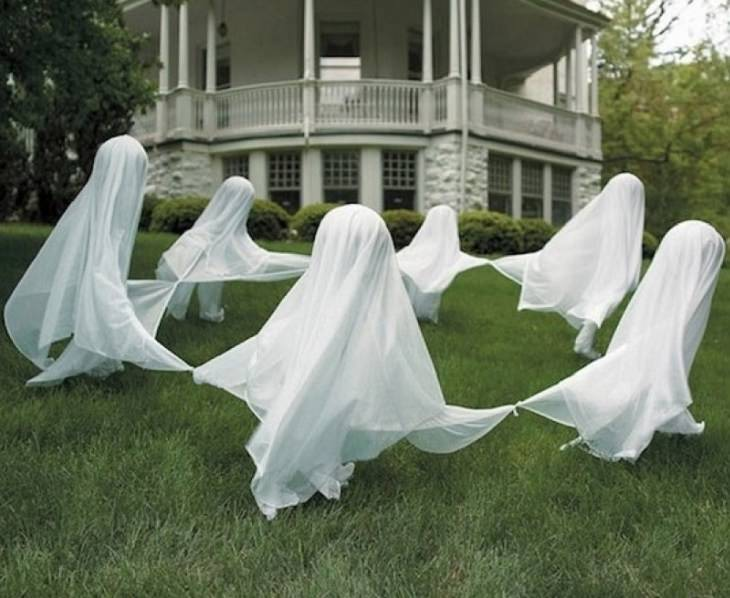 Most Incredible Halloween Decorations, ghost figures under white cloaks in a garden