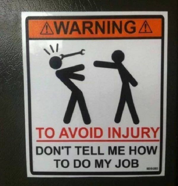 Funny warning and caution signs, funny warning sign of a person throwing a wrench at another stating that injury can be avoided by not telling one how to do their job