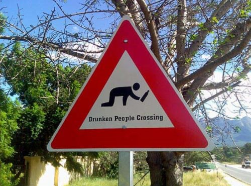 Funny warning and caution signs, Funny road sign displaying a drunk man on all fours with a bottle in his hand