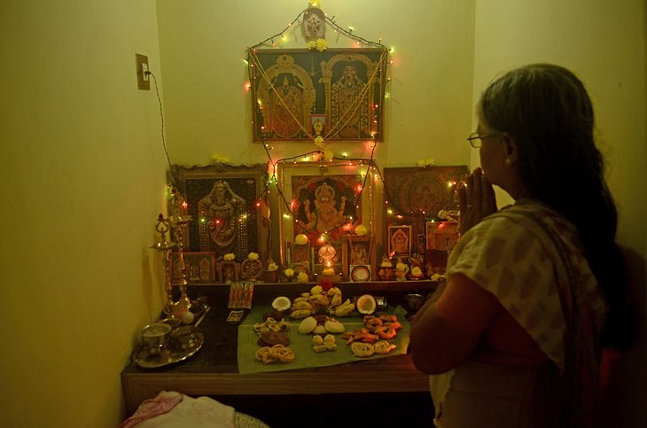 Photos from Diwali, the festival of lights, A Home pooja area on Diwali, with special food laid out for the Gods, depicted in the framed photographs, and new clothes laid out to be blessed.