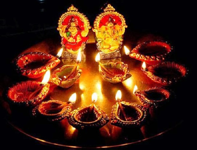 Photos from Diwali, the festival of lights, Small idols of the Deities Lakshmi and Ganesha, on a plate with multiple decorative Diyas, during celebrations in Sri Lanka