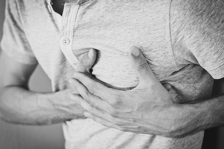 Scientists 3-D print heart with human tissue, black and white photo of man holding both hands to his chest in pain