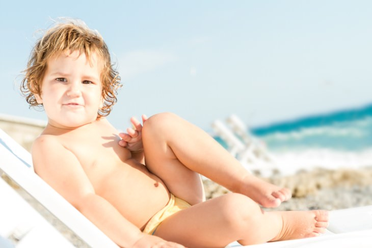 joke: baby boy sitting on a chair on the beach