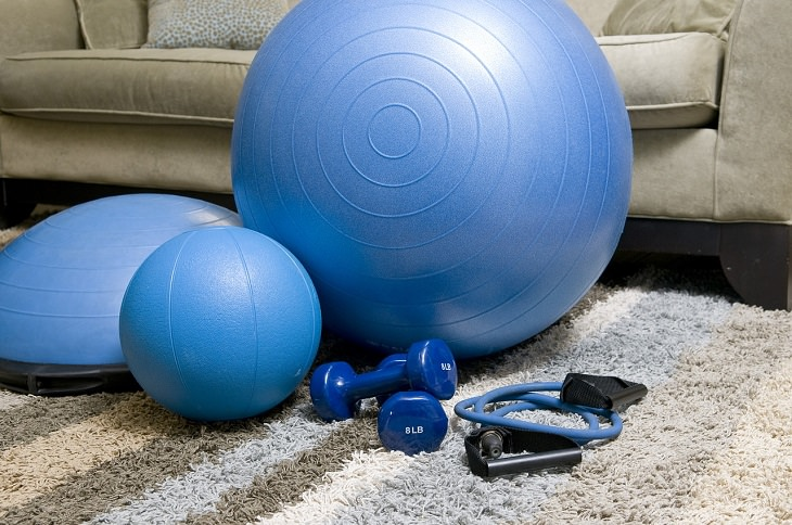 Exercising before food is beneficial to health. blue exercise equipment including exercise ball and dumbells