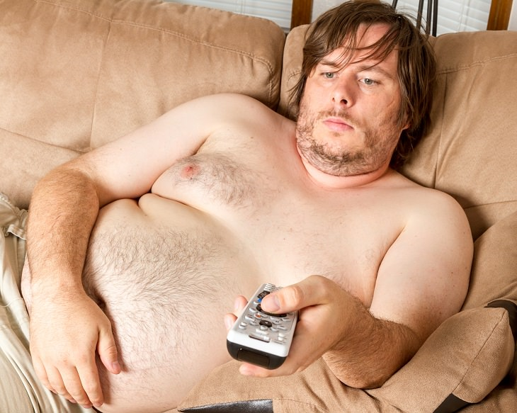 Exercising before food is beneficially to health. shirtless overweight man with brown hair and beard sitting on a sofa with a TV remote in his hand