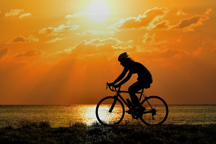 Exercising before food is beneficially to health. person wearing helmet cycling next to the ocean at sunrise