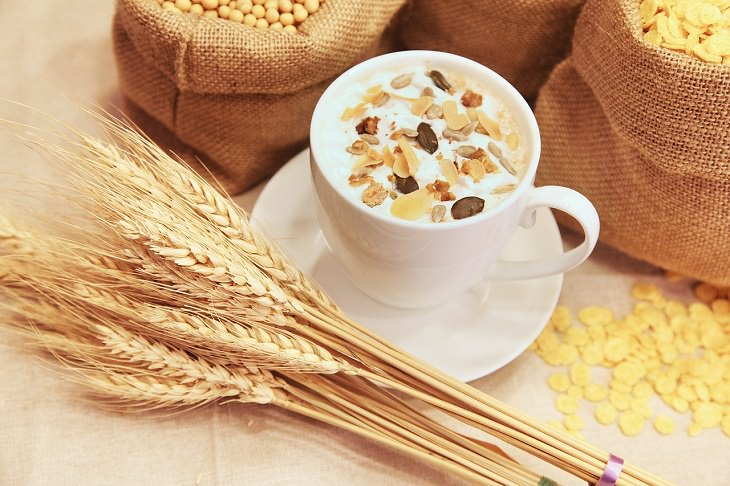 Exercising before food is beneficially to health. white bowl and plate with milk and cornflakes with dry fruit next to stalks of wheat and grains
