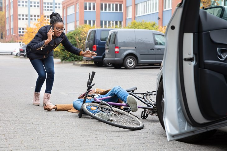 the dutch reach method of opening car doors for safety, woman on the phone calling an ambulance after hit a cyclist with her car door