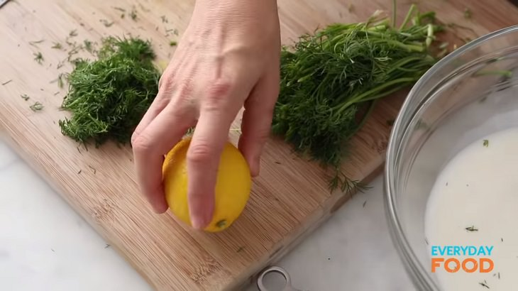 Simple and easy recipe for golden chicken with buttermilk marinade, bowl of marinade with lemon and fresh dill on a cutting board