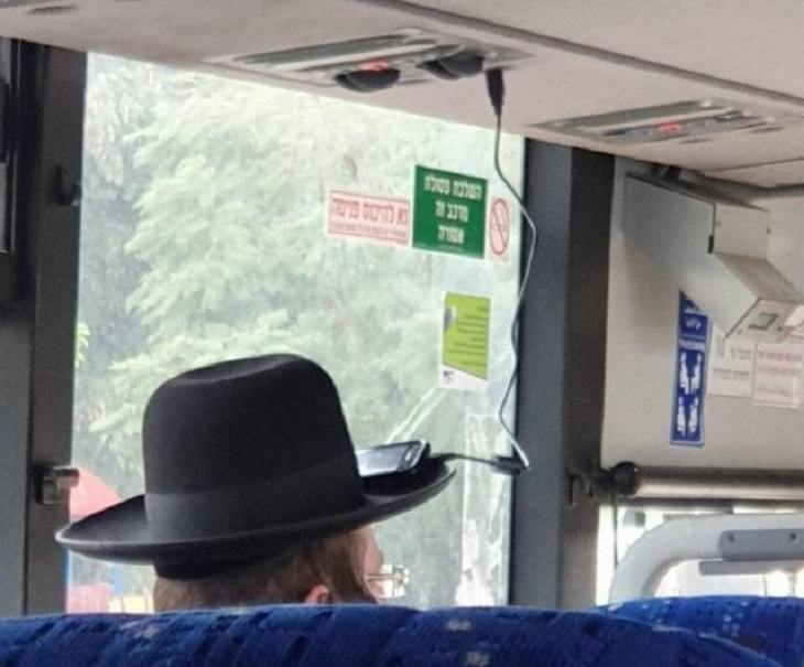 Hilarious but Smart Life Hacks, Man with large hat charging phone on charger over head with phone resting on the rim of the hat