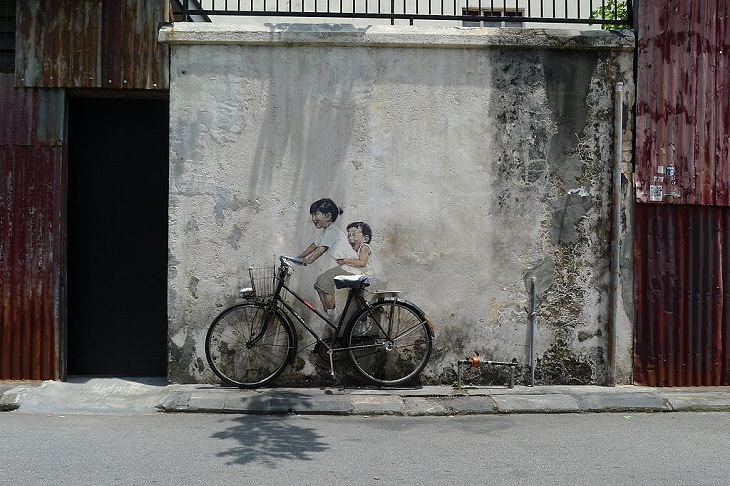 Beautiful Street art and graffiti murals from around the world, painting on a wall of two children riding a bicycle