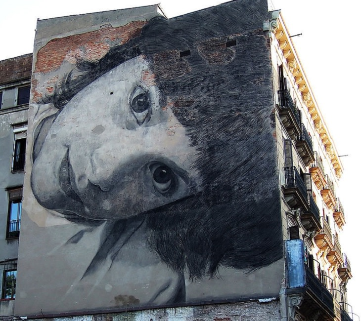 Beautiful Street art and graffiti murals from around the world, mural on a building wall in black and white of a young girl's face