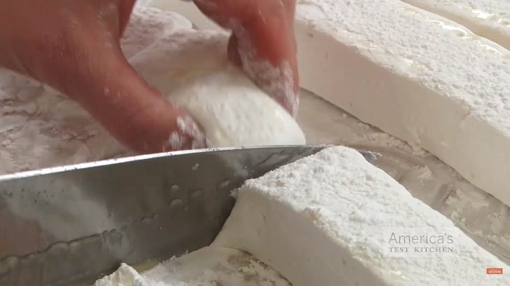 Perfect Recipe for Homemade marshmallows, white strips being cut into marshmallow cubes