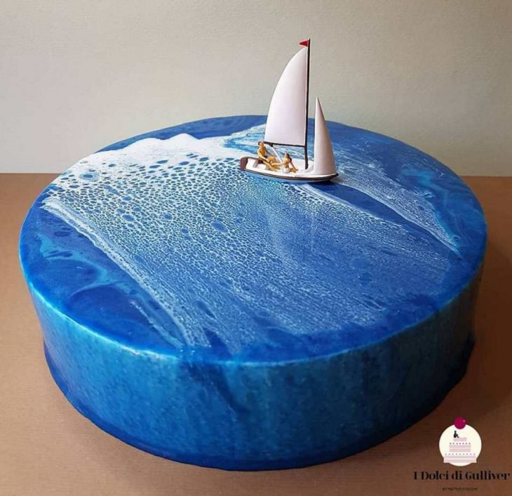 Beautiful Cakes Designed by Italian Chef, Large blue cake with added white coloring and small sailboat on top with two figurines inside