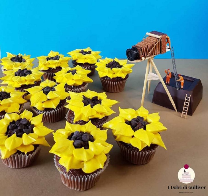 Beautiful Cakes Designed by Italian Chef, Many cupcakes with icing in the shape of sunflowers and two small figures next to it with a large chocolate old camera