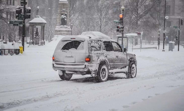 Helpful Winter Life Hacks On a Budget for dealing with Ice, Frost and Snow, car covered in snow on the road