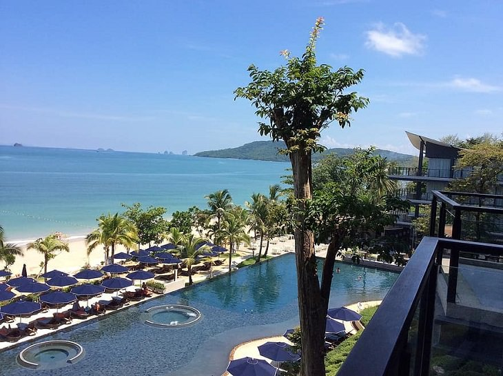 The sights, destinations and fun activities of cultural hub and land of beaches, Krabi in Thailand, resort with pool and view of the beach with lots of large umbrellas