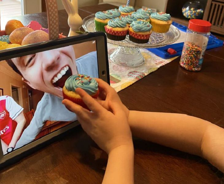Funny and heartwarming pictures of birthday celebrations during the COVID-19 pandemic quarantine and lockdown, child pretending to feed a cupcake to a man through a video call on an iPad