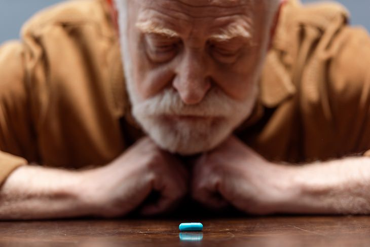 Debunking the myths about mental health, old man with white hair and beard in orange shirt looking at blue pill on table