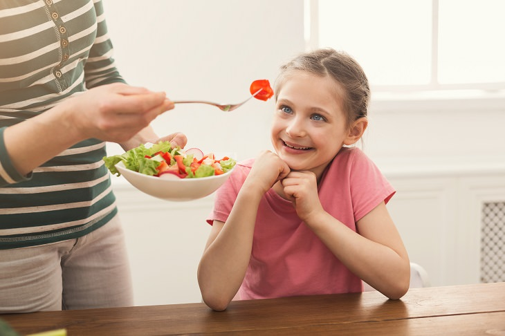 8 tips and tricks to help children develop healthy eating habits, Woman offering her daughter salad
