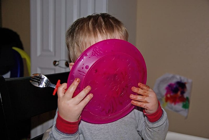 8 tips and tricks to help children develop healthy eating habits, Toddler with messy hands holding pink plate