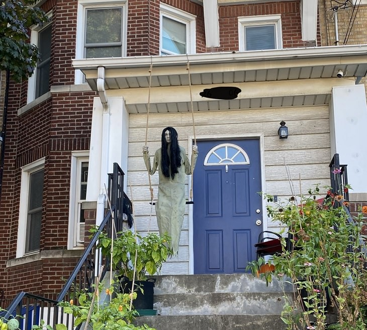 Creative and spooky halloween decorations from 2020, Mannequin in front of a house of young girl with long hair in a nightdress on a swing