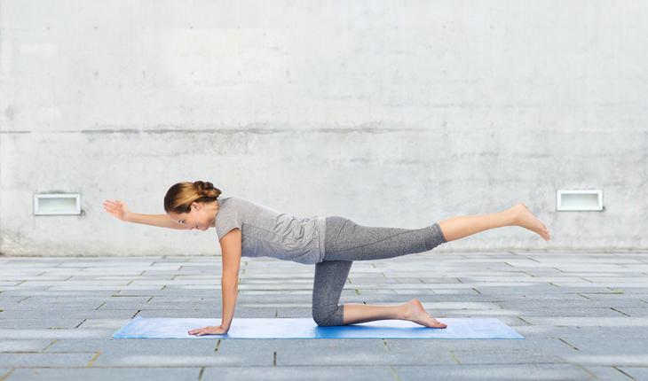 young woman doing Balancing Table  yoga position