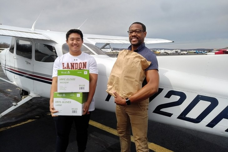 Best feel good stories of 2020, Teenager T.J Kim and flight instructor Dave Powell holding boxes of supplies donated to Page Memorial Hospital