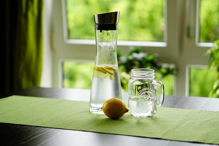 Drinks healthy to have while fasting, Bottle of water, mug of water, and lemon on a table