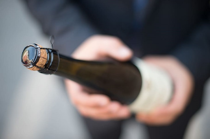 5 old rules of etiquette that we need to keep alive, Person holding a wine bottle