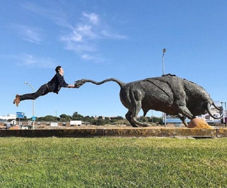Incríveis ilusões ópticas criadas pelo artista e fotógrafo de Portugal Tiago Silva, o homem segura a estátua de um touro pela cauda enquanto está no ar
