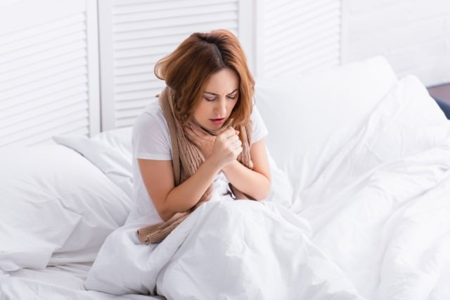 woman in bed coughing