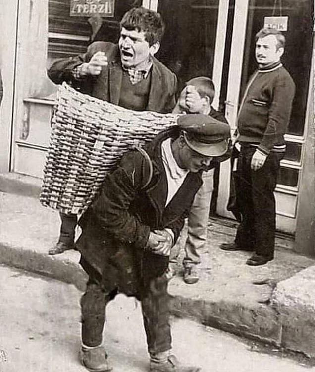 Historic photographs, An intoxicated man is taken home by a basket man employed at a bar in Turkey in the 1960's