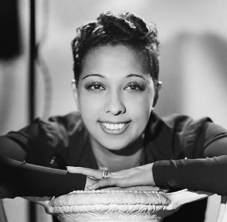 Josephine Baker: Siren of the Resistance, Studio photo of young Josephine Baker with her hands resting on a small table