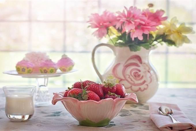 table with bowl of strawberrys glass of milk and vase