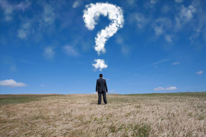 man in field with question mark in clouds
